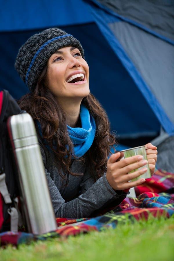 Fotvandrare som har en kopp kaffe i tält royaltyfri fotografi