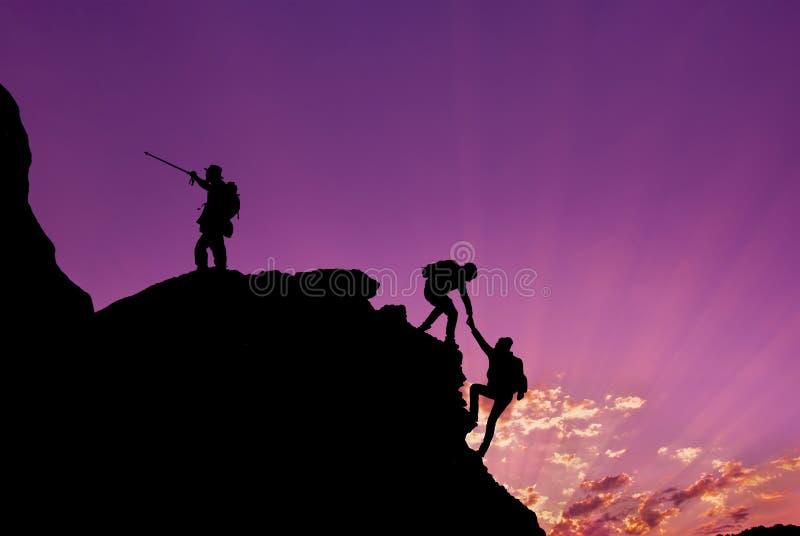 Fotvandrare som klättrar på, vaggar, berget på solnedgång, ett av dem som ger handen och hjälper att klättra Teamwork, hjälp, fra royaltyfri foto