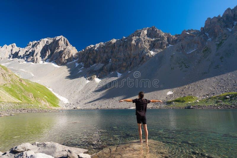 Fotvandrare som kopplar av på blåttsjön för hög höjd i den idylliska uncontaminated miljön som täckas en gång av glaciärer Sommar arkivfoton