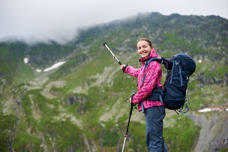 Fotvandrare som pekar med en trekking pinne på ett berg arkivfoto