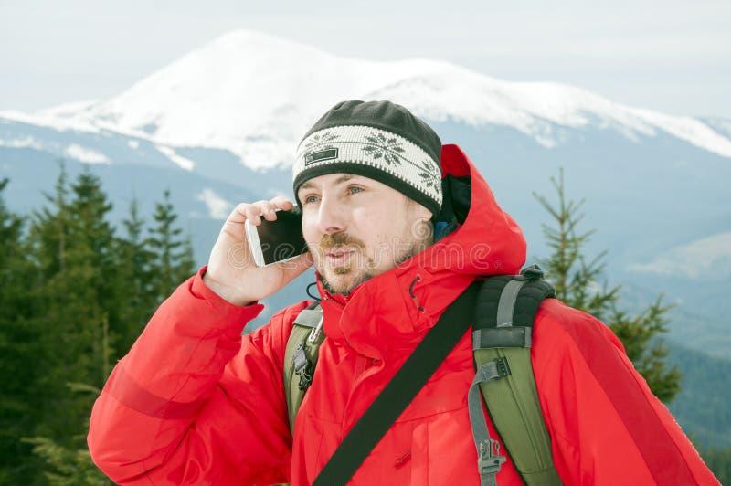 Fotvandrare som talar på smartphonen i vinterbergen royaltyfria foton