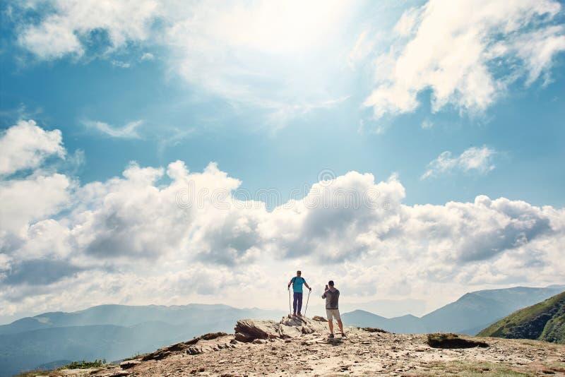 Fotvandrare som tycker om sikten och tar foto på bergkant Carpathians Ukraina royaltyfri foto