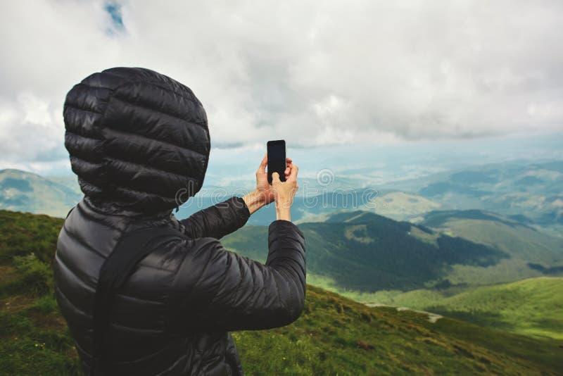 Fotvandrare som tycker om sikten och tar foto vid telefonen på bergkant Carpathians Ukraina arkivfoton