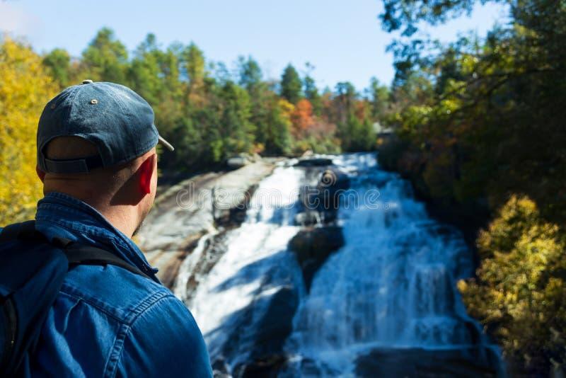 Fotvandrare som tycker om skönheten av höga nedgångar i Du Pont tillståndsskog i nedgången royaltyfria bilder