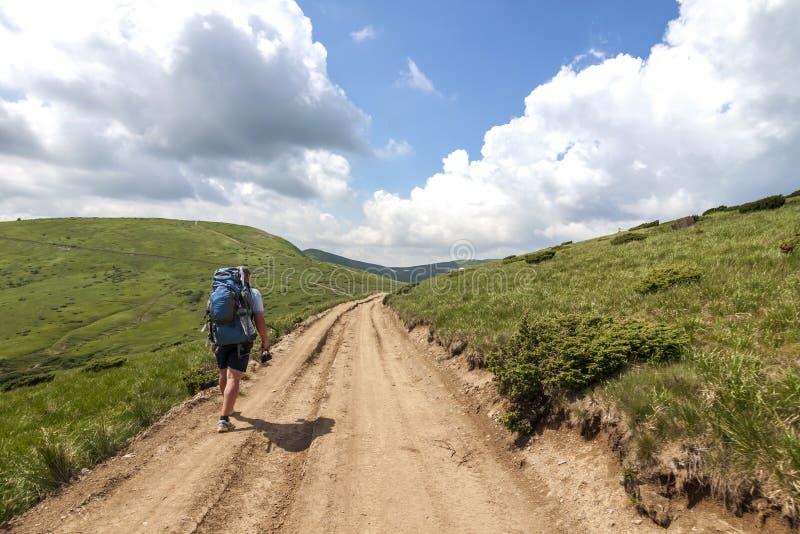Fotvandrare som upp klättrar berget i solig dag för sommar arkivfoton