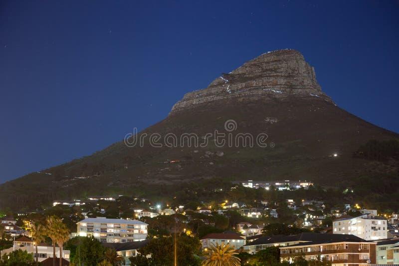 Fotvandrare stiger ned lejonets huvudmaximumet i Cape Town på natten royaltyfri fotografi