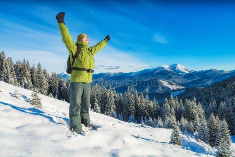 Fotvandrareanseende på en snöig kulle med lyftta händer royaltyfria bilder