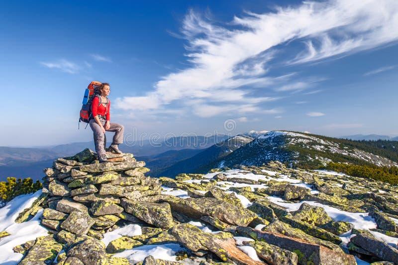 Fotvandrareflicka med ryggsäcken i berg royaltyfri fotografi