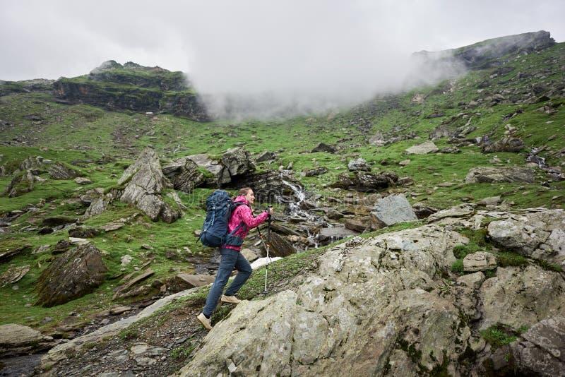 Fotvandrareflicka som klättrar upp i gröna steniga berg royaltyfri fotografi