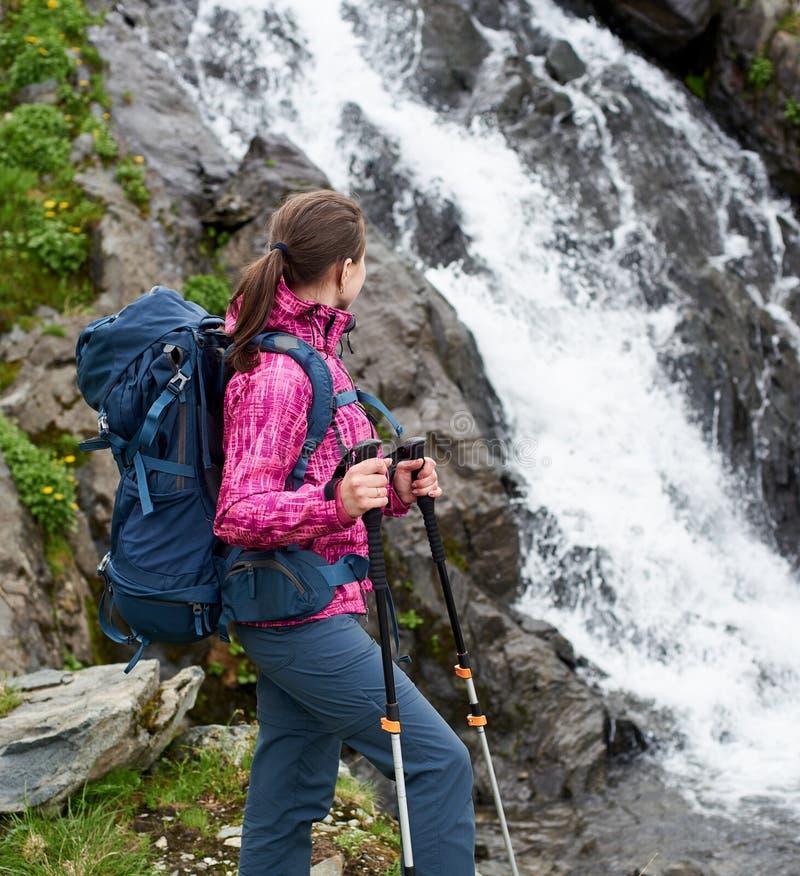 Fotvandrareflicka som ser på en stor bergvattenfall fotografering för bildbyråer