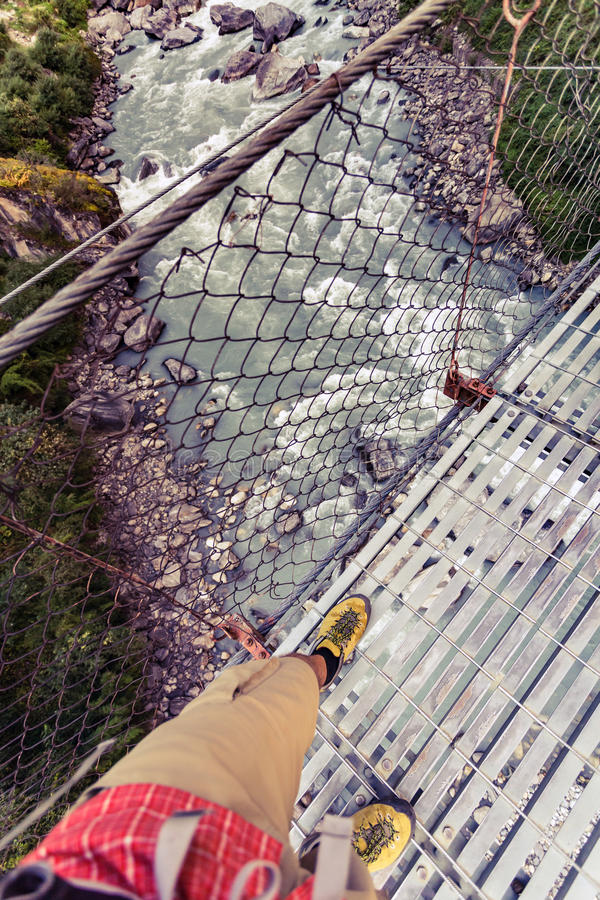 Fotvandrarekorsning upphängningbro och se ner i Himala arkivfoto