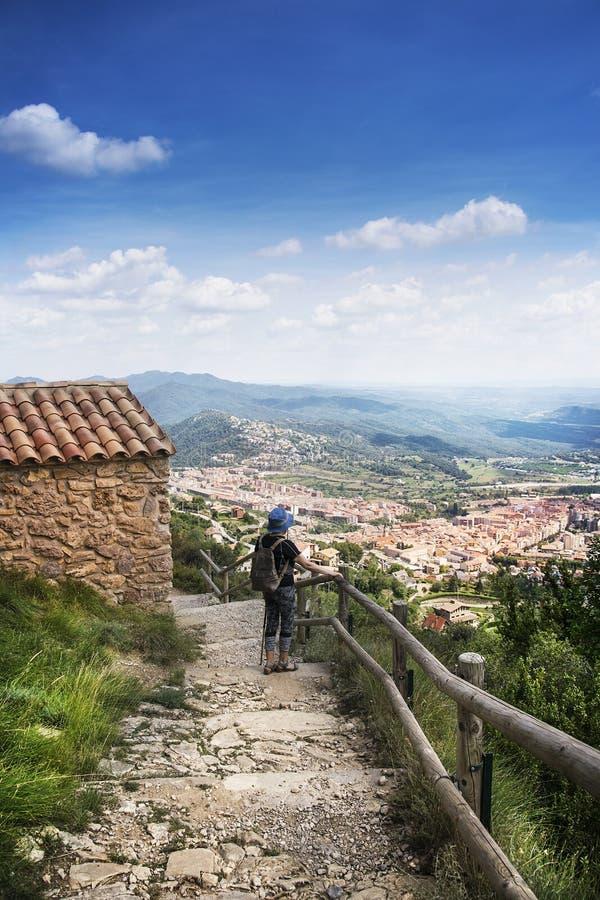 Fotvandrarekvinna bredvid en eremitboning på överkanten av den Queralt fristaden i Pyreneesna, Catalonia tomt kopieringsutrymme royaltyfria foton