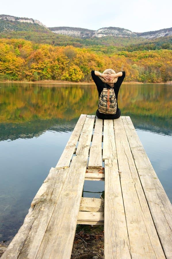 Fotvandrarekvinna som sitter över sjön i höstlig dag royaltyfri foto