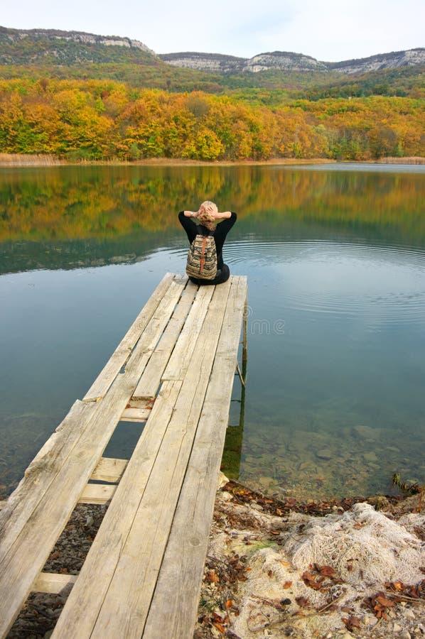 Fotvandrarekvinna som sitter över sjön i höstlig dag arkivbild