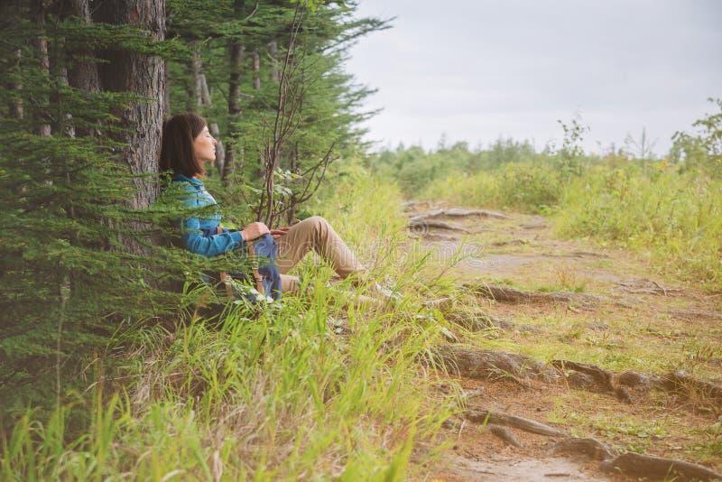 Fotvandrarekvinna som vilar nära trädet i skog royaltyfria foton