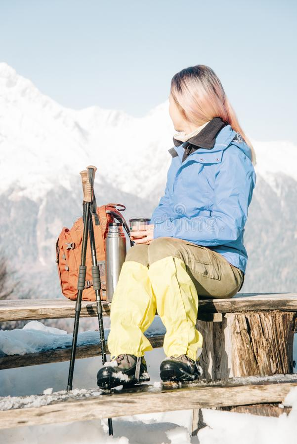 Fotvandrarekvinna som vilar på träbänk i vinter royaltyfri bild