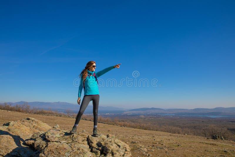 Fotvandrarekvinnaanseendet vaggar på i det Madrid berget som pekar med handen arkivfoton