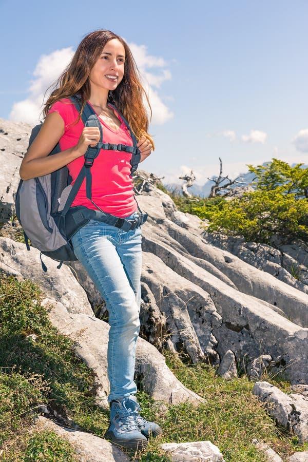 Fotvandrarekvinnaanseendet vaggar på och hålla ögonen på landskapet fotografering för bildbyråer