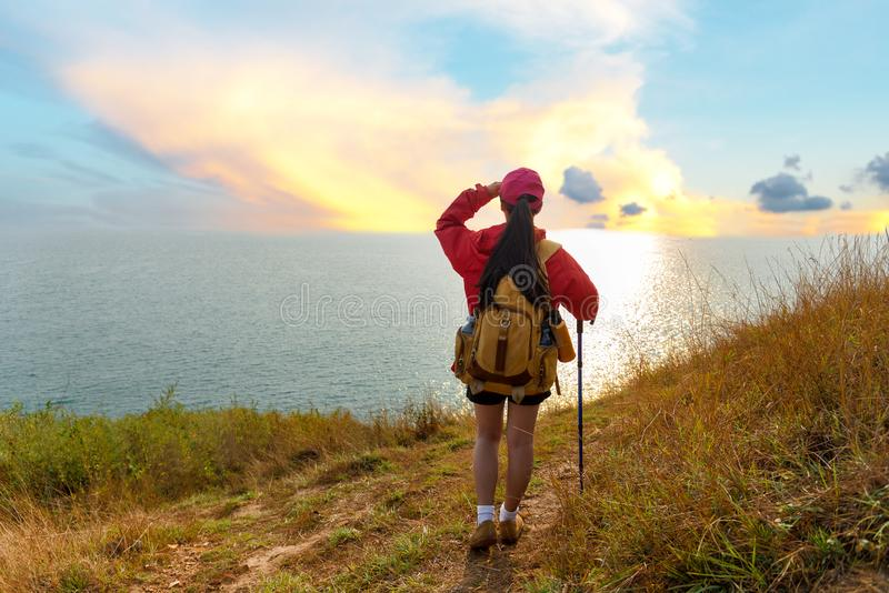 Fotvandrarekvinnan klättrar upp det sista avsnittet av solnedgången i berg nära havet Handelsresande som går i utomhus- royaltyfri bild
