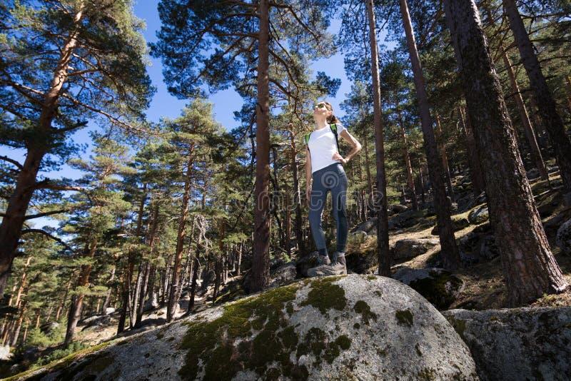 Fotvandrarekvinnan som poserar på ett stort, vaggar i skog fotografering för bildbyråer