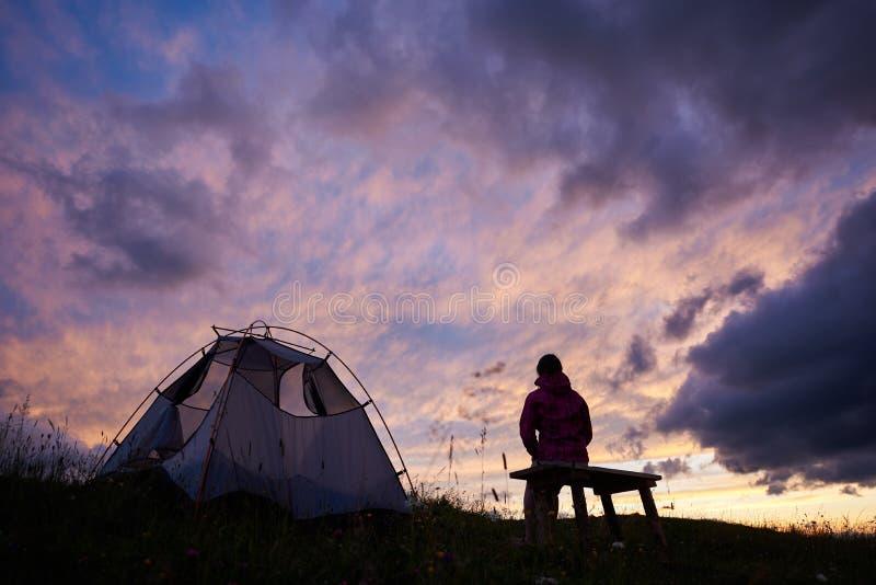 Fotvandrarekvinnasammanträde på en bänk nära tältet på solnedgången royaltyfria bilder