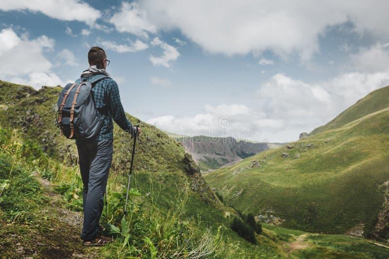 Fotvandrareman med ryggsäcken och Trekking Poles som vilar och ser bergen i utomhus- sommar, bakre sikt royaltyfri foto