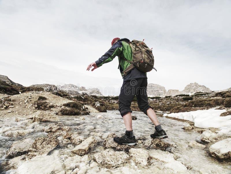 Fotvandrareman med ryggs?ckkorsningen str?m p? stenar i Dolomiti royaltyfria foton