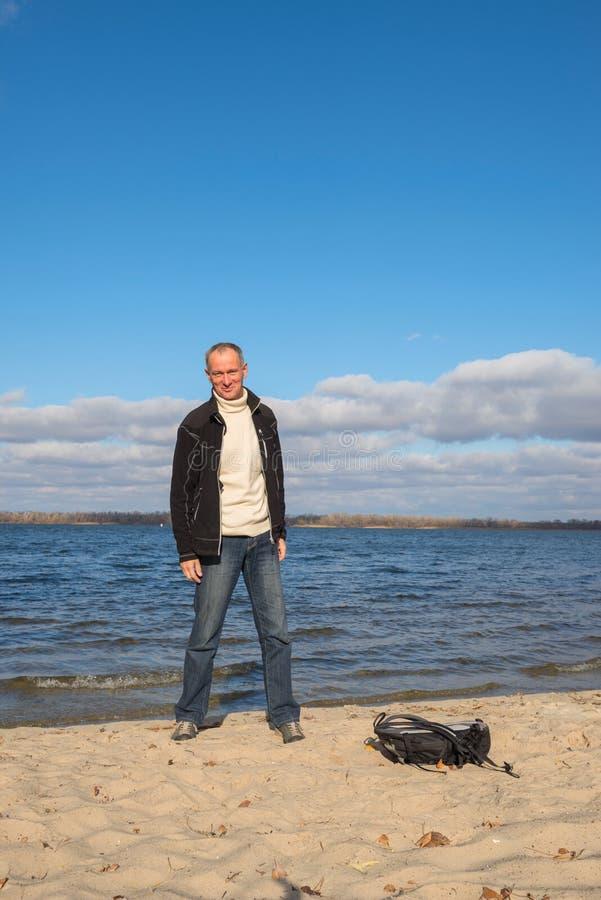Fotvandraremananseende på stranden och att koppla av, le och havande fu royaltyfria foton
