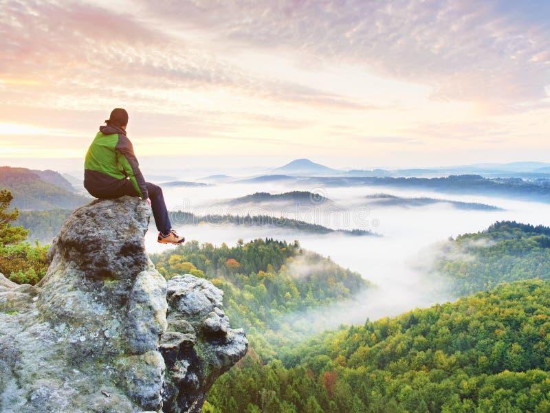 Fotvandraremannen tar en vila på bergmaximum Man sitter på skarp toppmöte och tycker om spektakulär sikt fotografering för bildbyråer