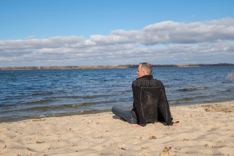 Fotvandraremansammanträde på stranden, tillbaka till kameran som ler, relaxin royaltyfria bilder