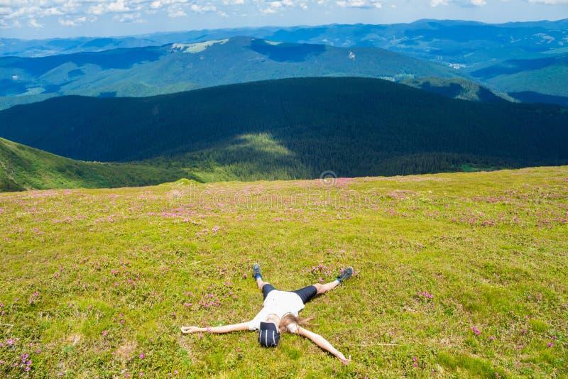 Fotvandraren för den unga kvinnan ligger på överkanten av kullen och tycker om härlig bergdalsikt arkivfoton