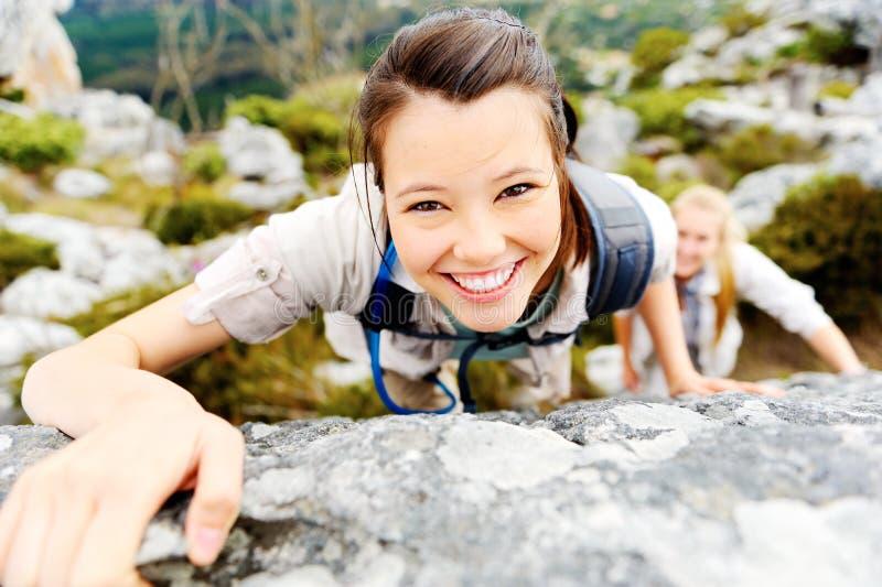 Fotvandraren ler, medan klättra upp en stenig vägg royaltyfria foton