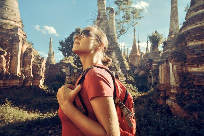 Fotvandraren med ryggsäcken och undersöker buddistiska stupas i Burma royaltyfria foton