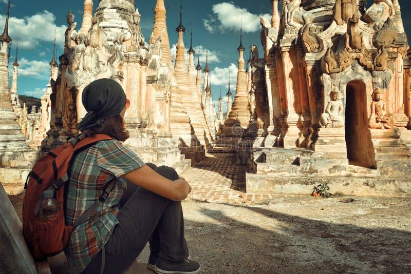Fotvandraren med ryggsäcken sitter och ser buddistiska stupas i Burma royaltyfria bilder