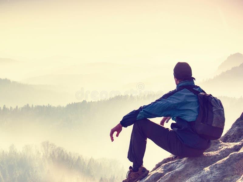 Fotvandraren tycker om soluppgångsikt i bergigt landskap Manligt fotvandraresammanträde fotografering för bildbyråer