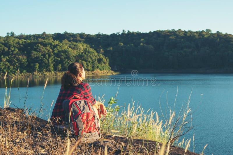 Fotvandraresammanträde för den unga kvinnan på bergmaximumet, nedanför henne är stor lak arkivfoton