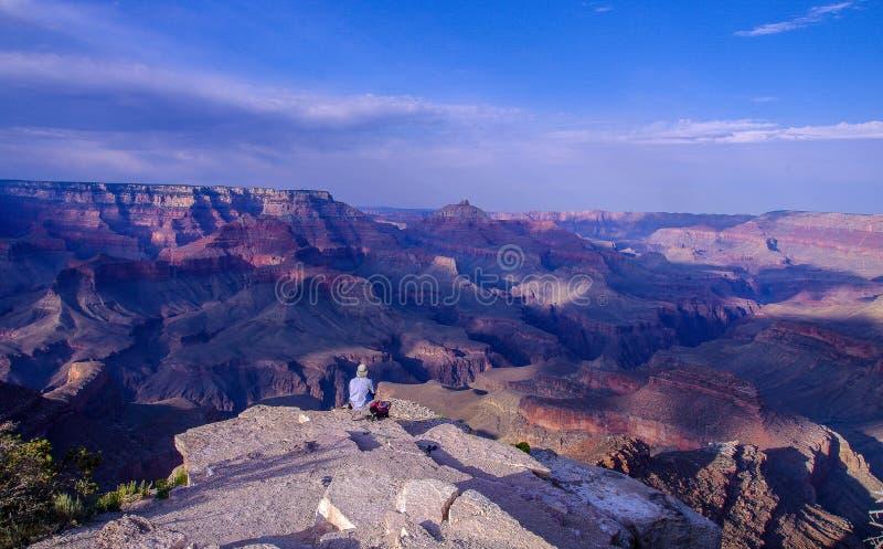 Fotvandraresammanträde på kanten av vaggar utlöparen med panoramautsikten av Grand Canyon royaltyfria bilder