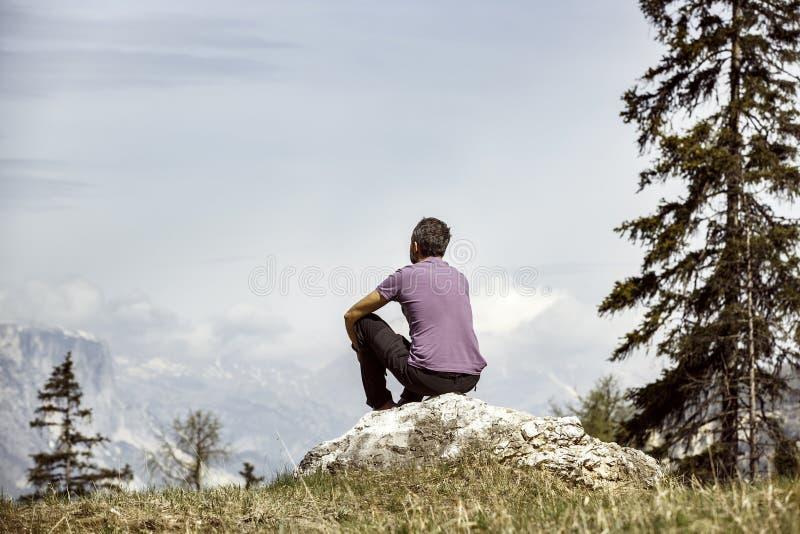 Fotvandraresammanträde vaggar på på en bergöverkant i alpint landskap royaltyfri foto