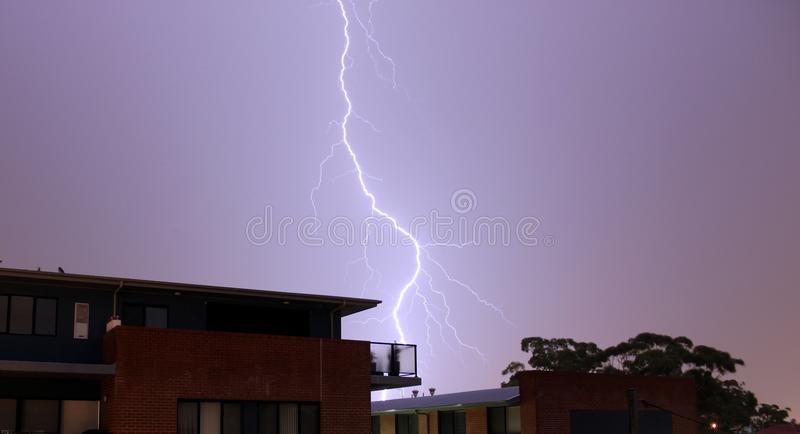 Foudre au-dessus des maisons en Australie image libre de droits