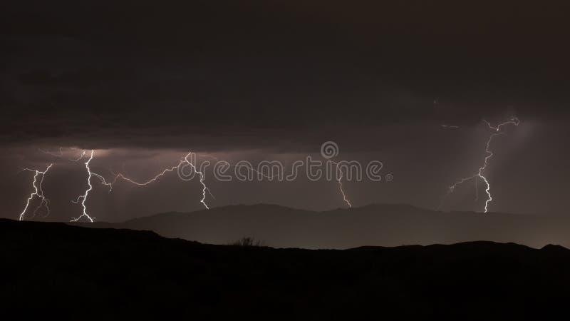 Foudre clignotant au-dessus des montagnes éloignées la nuit photo stock