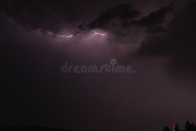 Foudre entre les nuages au ciel pourpre image stock