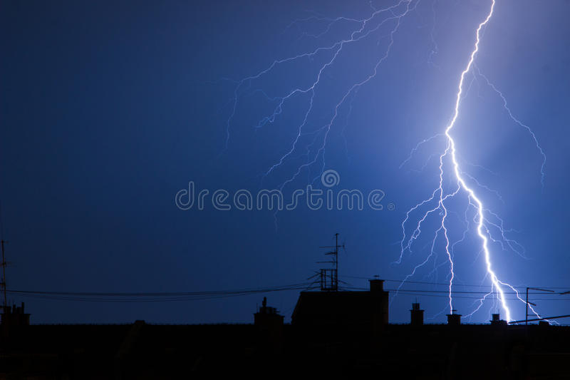 Foudre frappant des dessus de toit de bâtiment dans l'orage photographie stock