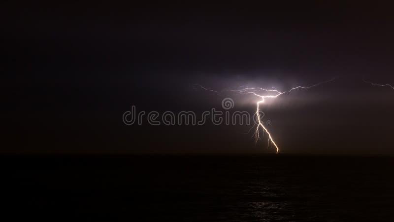 Foudre sur le ciel au-dessus de l'océan image stock