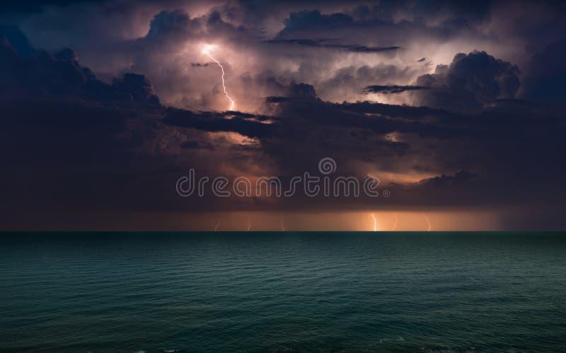 Foudres énormes en ciel orageux foncé au-dessus de mer de ondulation photographie stock