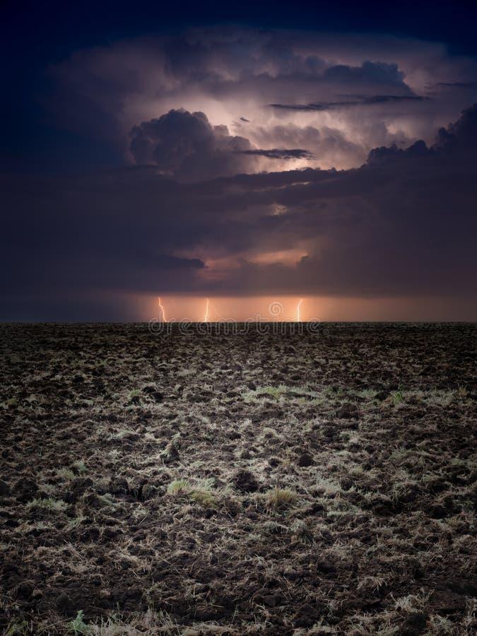 Foudres puissantes en ciel orageux foncé au-dessus de champ labouré de ferme photo stock