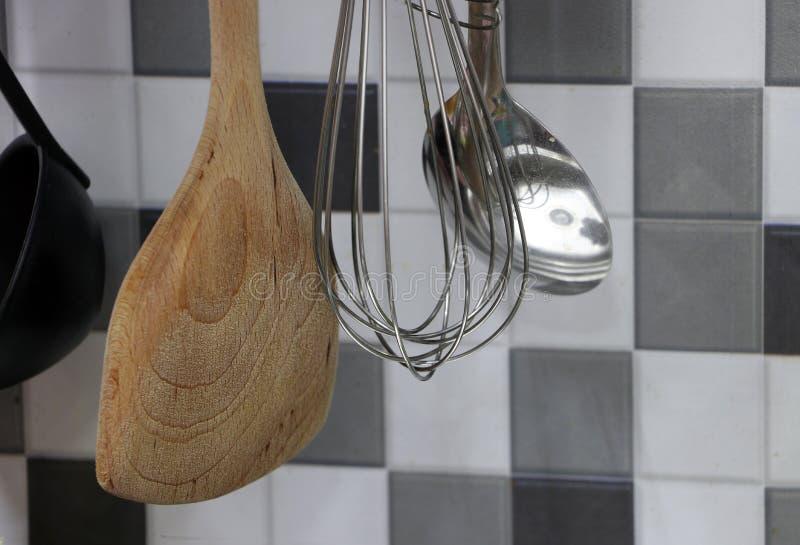 Fouet inoxydable d'oeufs avec la poche et la pelle en bois de la poêle accrochant dans la cuisine photos stock