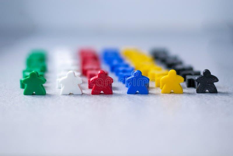 Foule de petites figures colorées des personnes comme concept de teambulding Meeples de jeu de société Stratégie commerciale et b image stock