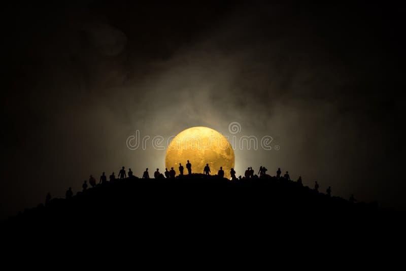 Foule effrayante de vue des zombis sur la colline avec le ciel nuageux fantasmagorique avec le brouillard et la pleine lune en ha photographie stock libre de droits