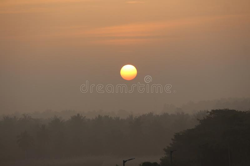 Found this scenic sunrise at a railway station near my place. Rage of the sun is increasing amd place is foggy and dull stock photo