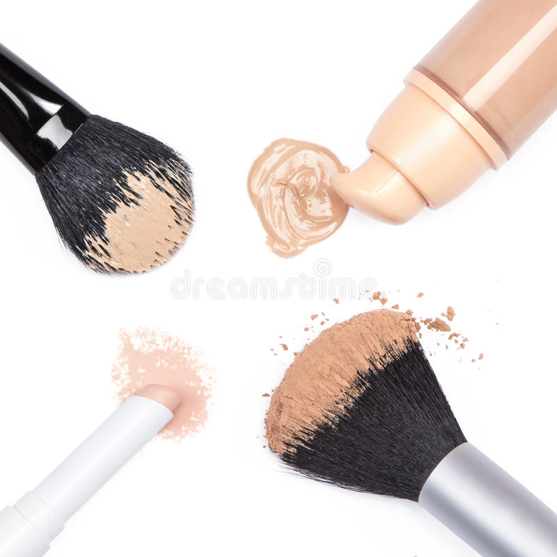 Foundation, concealer pencil and powder with makeup brushes stock photos